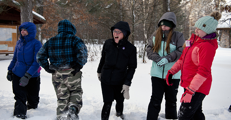 Sister Julia Walsh plays in snow with retreat guests