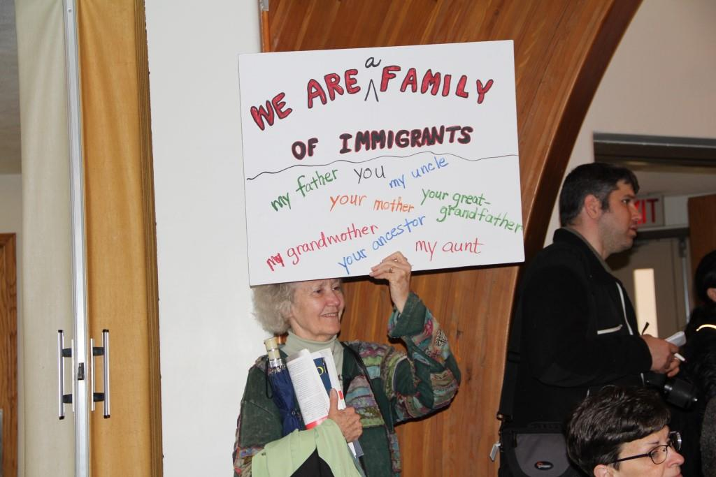 Sister Karen holding sign promoting families during immigration rally