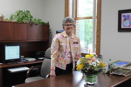 Sister Helen Elsbernd stands with flower bouquet