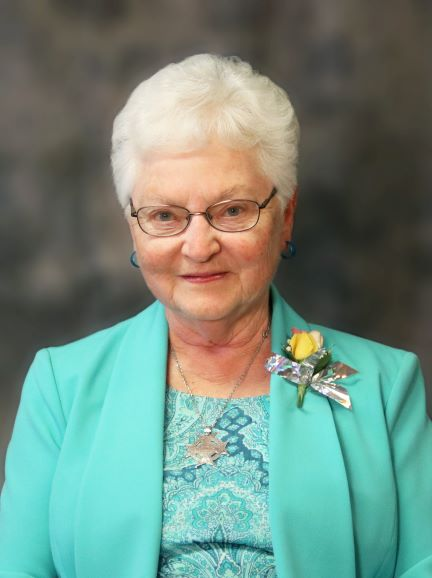 woman-turquoise-suit-white-hair-glasses-corsage