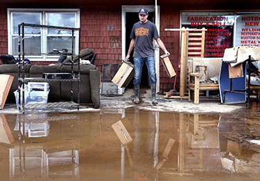 Dave Philips clears flood damage at his shop, DC Kustoms