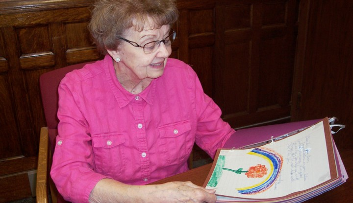 Sister Jean Ann looking at a scrap book