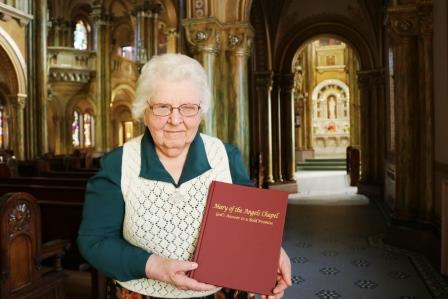 Sister Malinda Gerke poses in Mary of the Angels Chapel with her new book