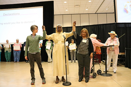 Franciscan Sister of Perpetual Adoration Kristin Peters, Little Sister of St. Francis Sarah Nakyesa and honored guest Reyna Mendez hold raised hands proclaiming A Revolution of Goodness