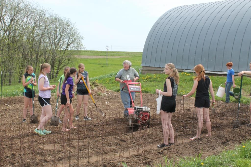 Sister Lucy Slinger gardening with students