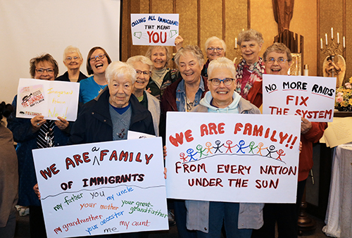 "Several Franciscan Sisters of Perpetual Adoration and staff hold signs saying ""We are family. From every nation under the sun."" ""We are family of immigrants."" ""No more raids! Fix the system."""