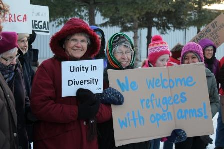 Two FSPA hold signs welcoming refugees