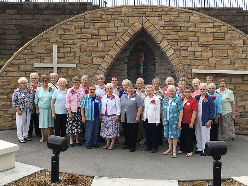 A group of Franciscan Sisters of Perpetual Adoration smile in front of the Garden View Grotto