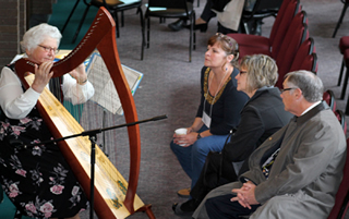 Sister Malinda Gerke plays the harp for conference participants