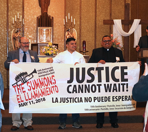 "Presenters celebrate ""The Summons"" at St. Bridget's Catholic Church on May 11, 2018, holding a sign that says ""Justice cannot wait! La justicia no puede esperar"""""