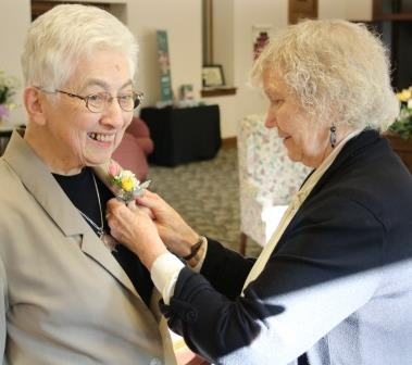 two-women-white-hair-corsage-pinning